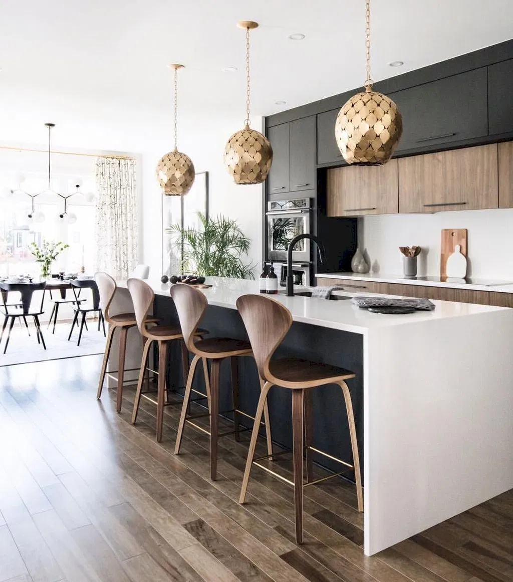 modern minimalist kitchen with black and wood cabinets, white countertops, wood floors and gold pendants