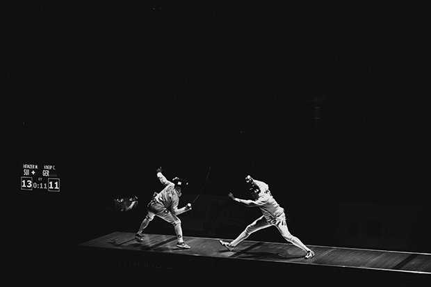 Black and white image of two fencers during a match