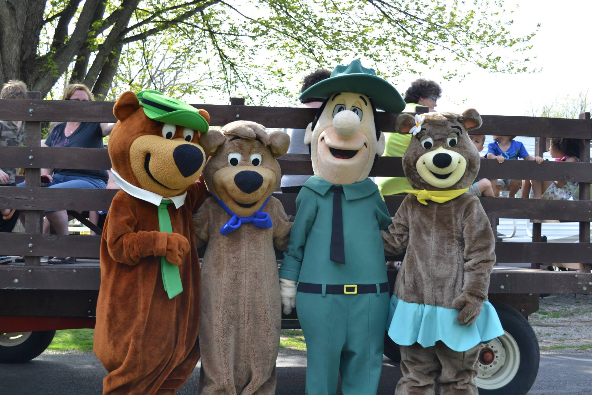 Yogi Bear characters in front of wagon ride.