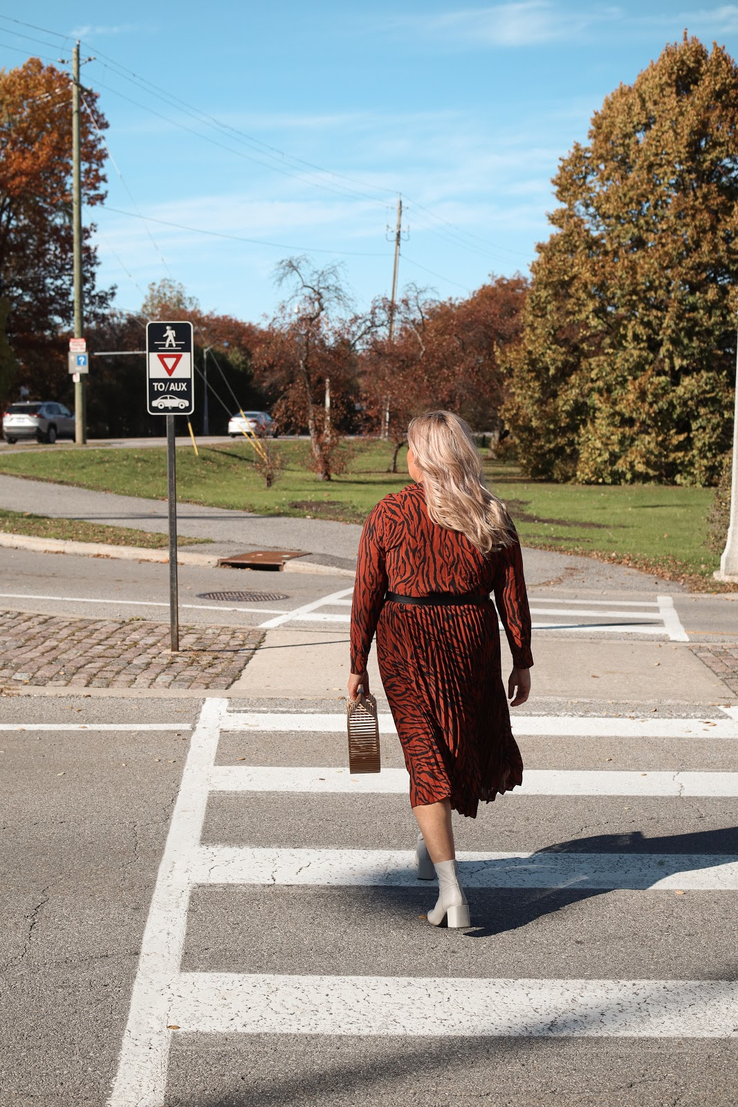 Allstate Takes Action'- roundabouts improve road safety in Ottawa. Fashion woman crossing the street.