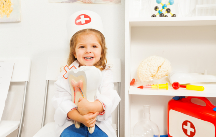 young girl playing dentist