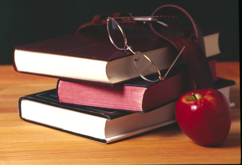 stack of books with glasses and an apple next to them.