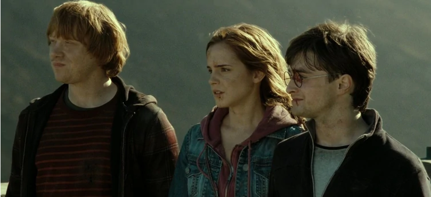 Still from Harry Potter and the Deathly Hallows, Part 2. L-R Ron, Hermione and Harry stand bloodied and bruised outside Hogwarts castle after the climactic battle. The sun is shining on them as they look out with expressions of mixed fear and relief.