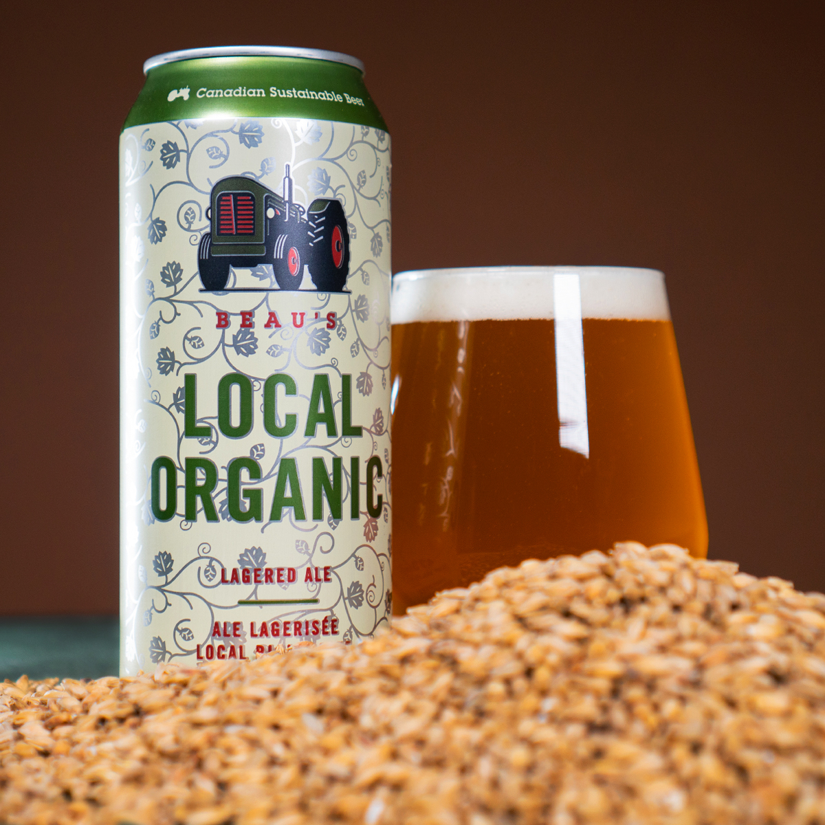 A can of Beau's local organic, beside a glass of the beer with grain in the foreground.