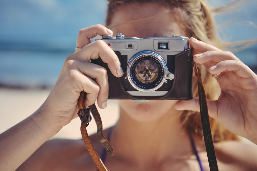 Young woman holding a camera: Essentials you need for your vacation