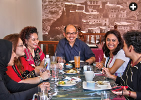 Just down the street, members of the Arab Network of Singapore meet at Zac's Cafe. Alwi Abu Baker Alkaff sits center, a picture of his community's Hadhramaut homeland in Yemen behind him.