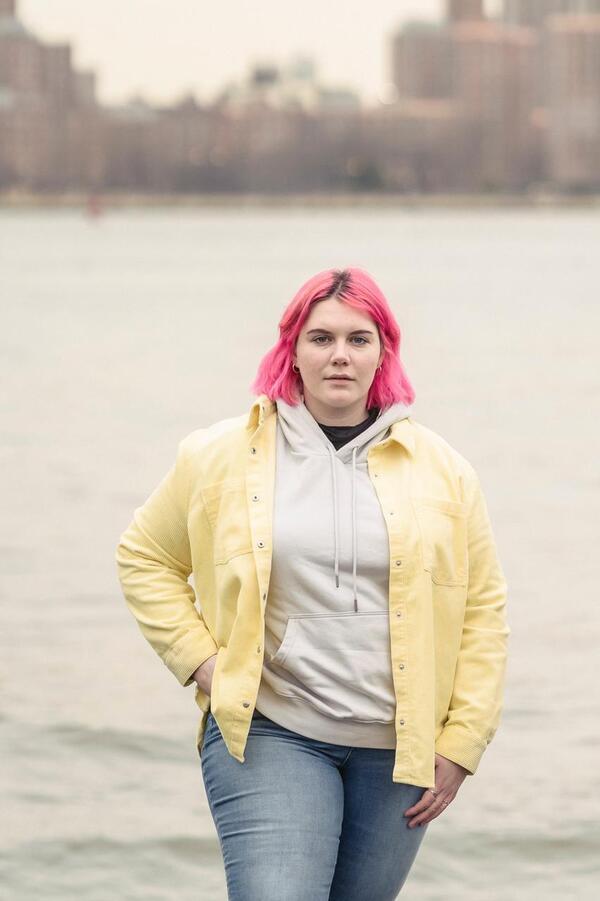 Mulher de cabelo rosa usando calça jeans, moletom e jaqueta de sarja amarela.