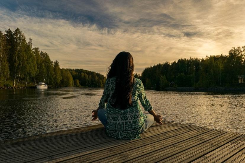 Chica haciendo yoga frente a un lago