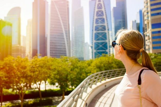 Girl with ponytail looks over her shoulder at great skyscrapers Free Photo