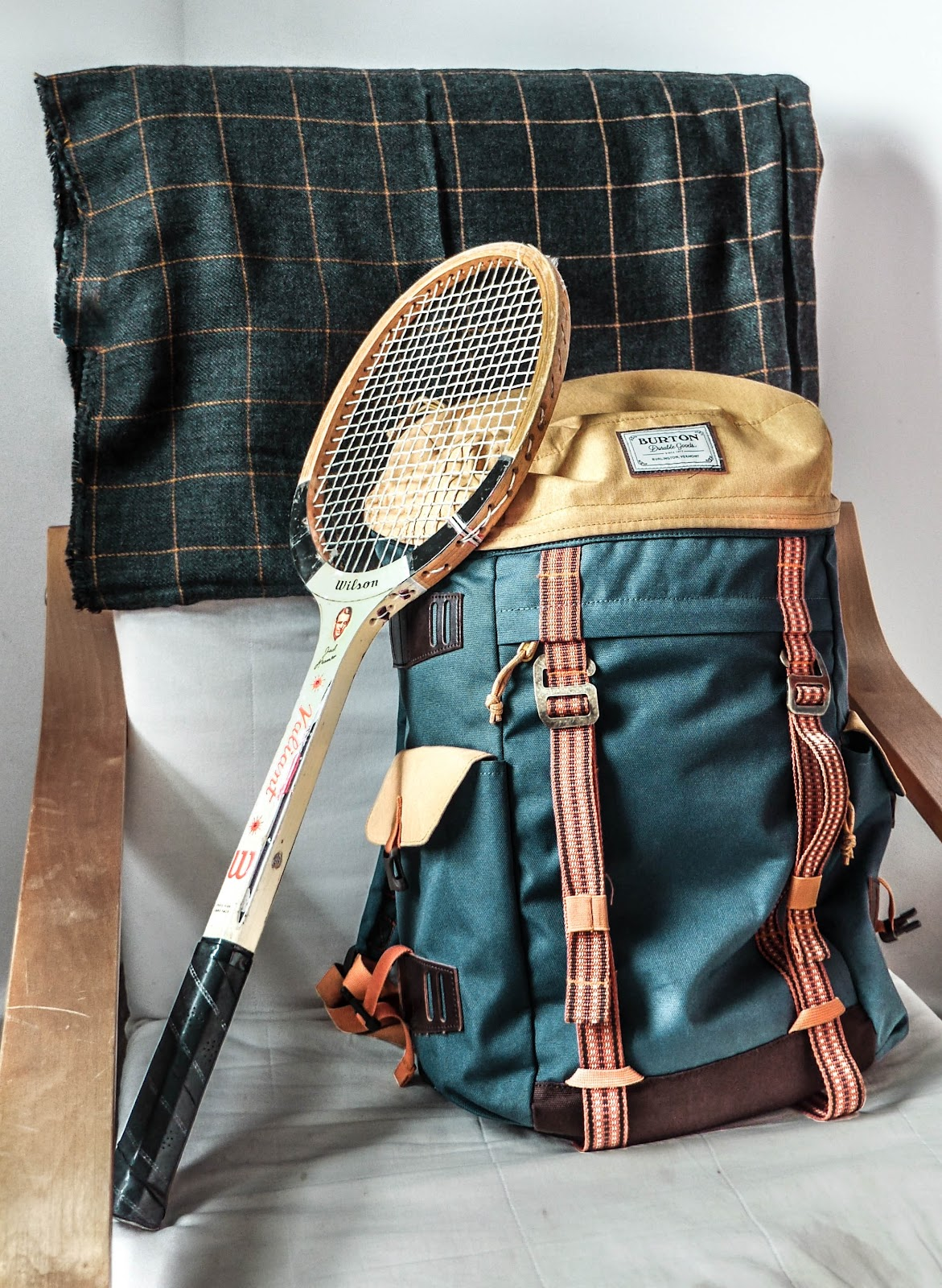 This is an older style Wilson badminton racket leaning up against a backpack that may hold badminton gear.  It may have been the best badminton backpack of it's era, but clearly doesn't fit today's styles.