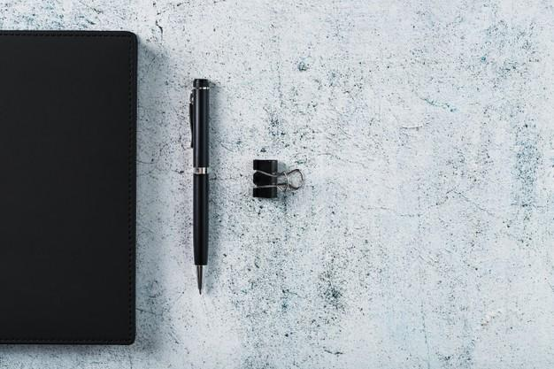 Black notepad with a black pen on a gray background. top view, minimalistic concept. free space. Premium Photo