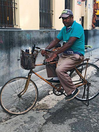 這位古巴大哥,腳踏車雖然停住沒騎,但他的雙腳不停的踩,產生動力,帶動前面鐵槓上面的磨刀石,他可在車上磨刀,不禁佩服古巴大哥的創意(楊仁烽攝影)