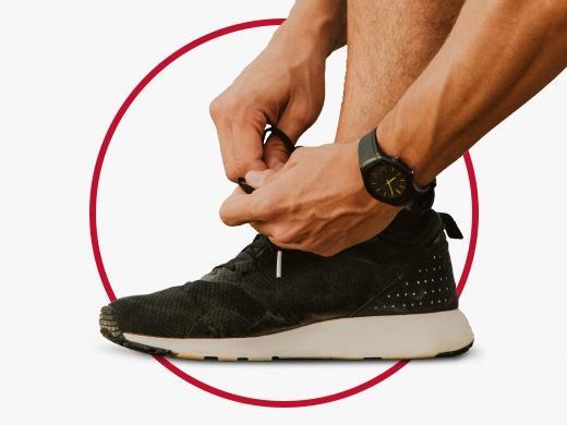 Sporty man with black watch tying shoe