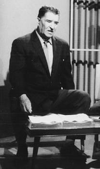 Imagen en blanco y negro de un hombre sentado en una silla  Descripción generada automáticamente con confianza media