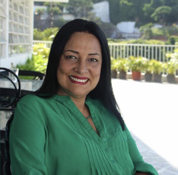 Mujer sonriendo con una camisa verde  Descripción generada automáticamente