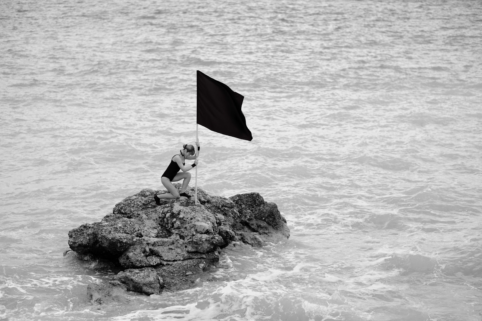 Black and white photo of a woman planting a black flag on a rock in the middle of the ocean.