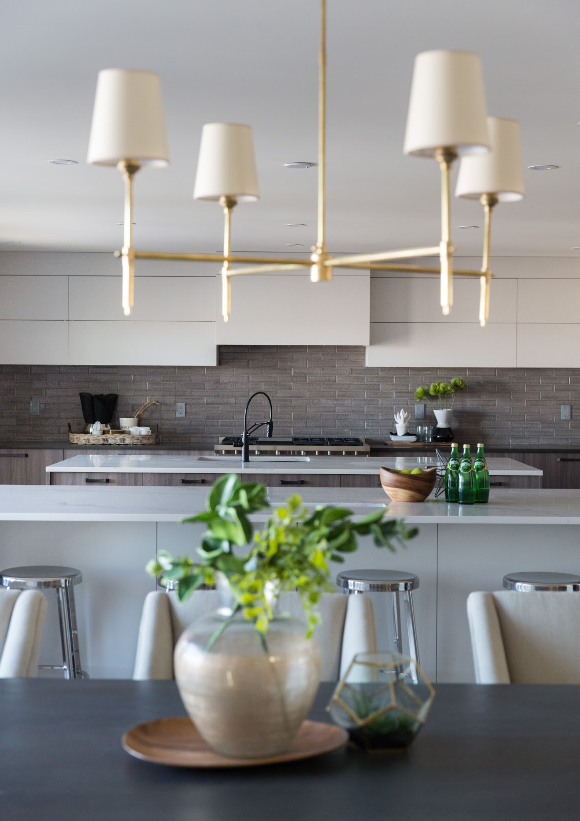 soft modern traditional lighting, textured tan backsplash double island calgary design