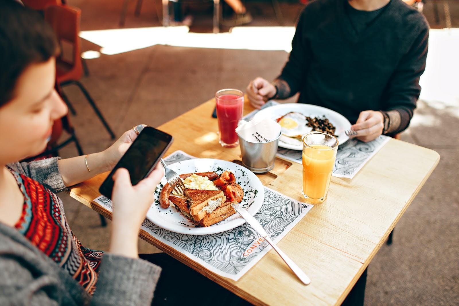 Duas pessoas sentadas em uma mesa e comendo.