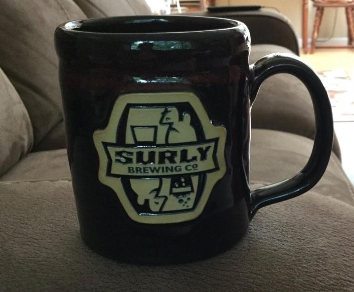 A brown coffee mug with a logo for Surly Brewing Company