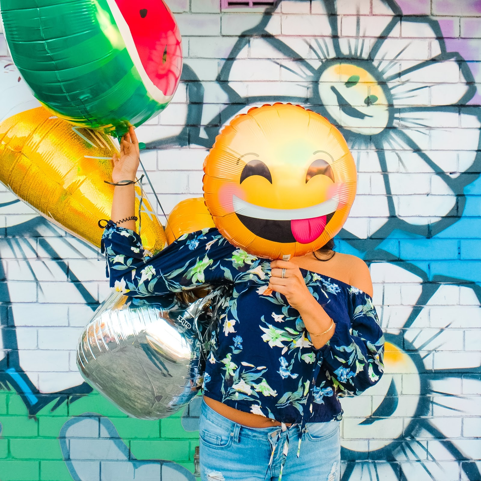 Woman with emoji balloon in front of their face
