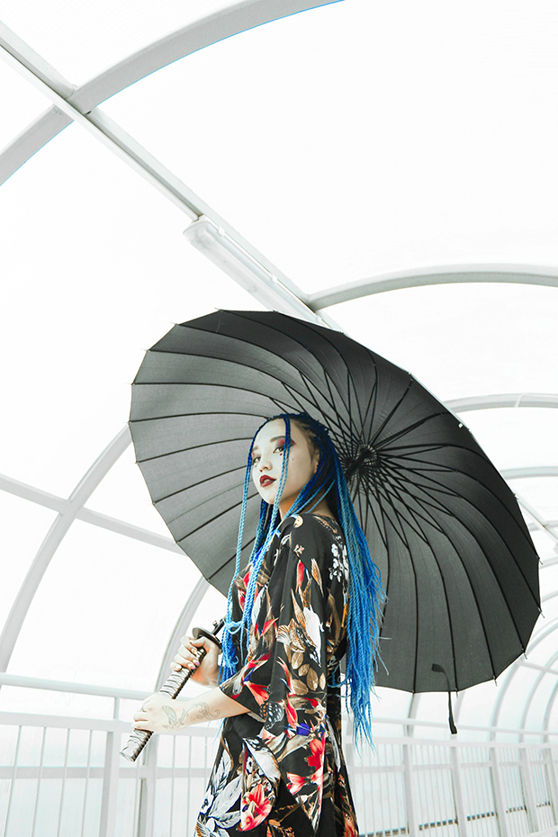 Well-lit image of a woman with blue dreadlocks and bold makeup holding a black parasol. She is wearing a serious expression and turned slightly toward the camera.