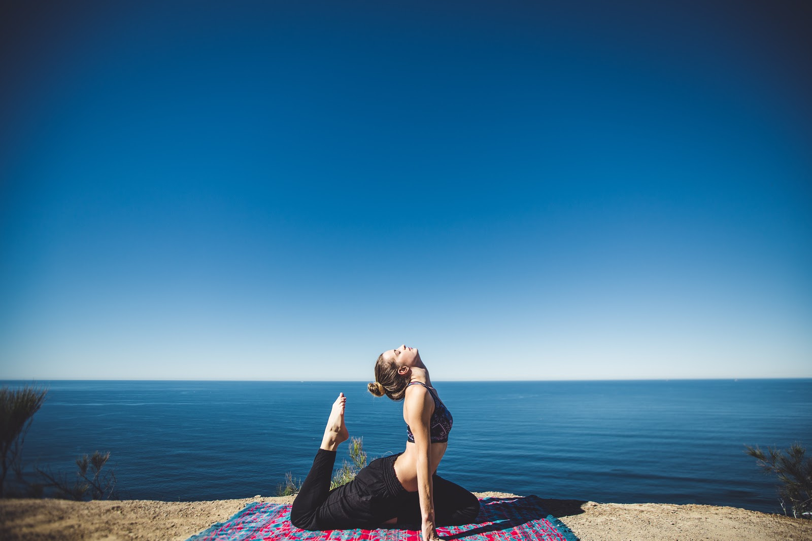 Gut cleanse: A woman does yoga in front of the ocean