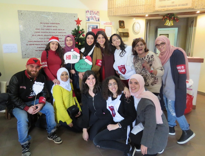 "Above, volunteer youth from the Order of Malta Lebanon, a Catholic organization, and ""Who Is Hussain?"" a Shiite Muslim organization, gather at the order's community health center in the Ain El Remmaneh suburb of Beirut Dec. 9 before heading out to decorate the homes of poor elderly Christians for Christmas. Below, volunteers pose with Gabriel and his sons, whom they visited Dec. 9 to decorate their Christmas tree."