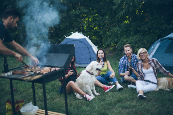 A family camping while someone cooks on an outdoor griddle