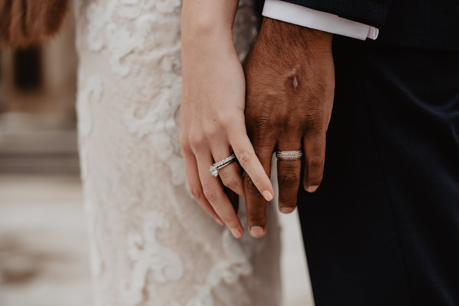 Image of married couple holding hands on wedding day.