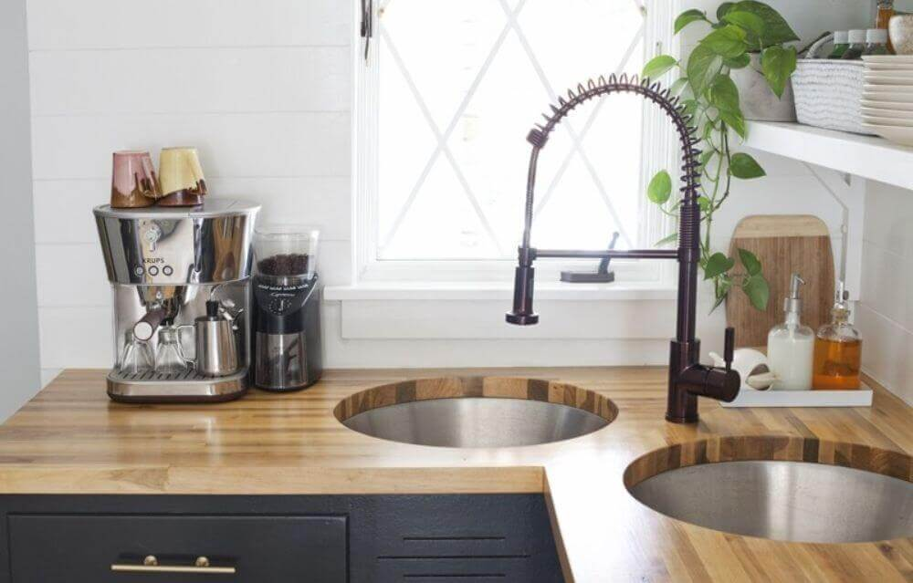 modern double basin corner sink with modern faucet and wood countertops