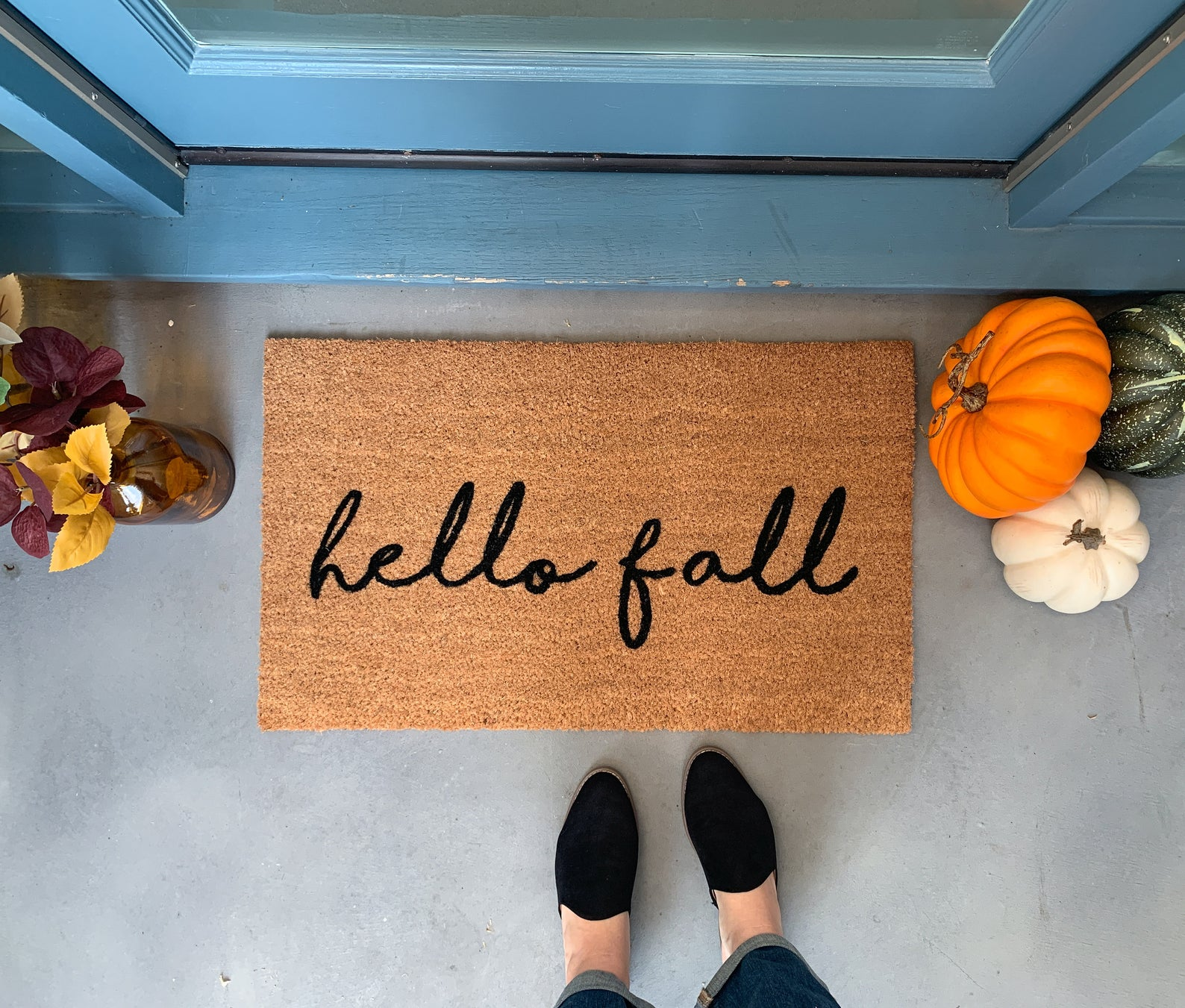Front door mat that reads hello fall and pumpkins orange white and green with a vase with colored leaves.