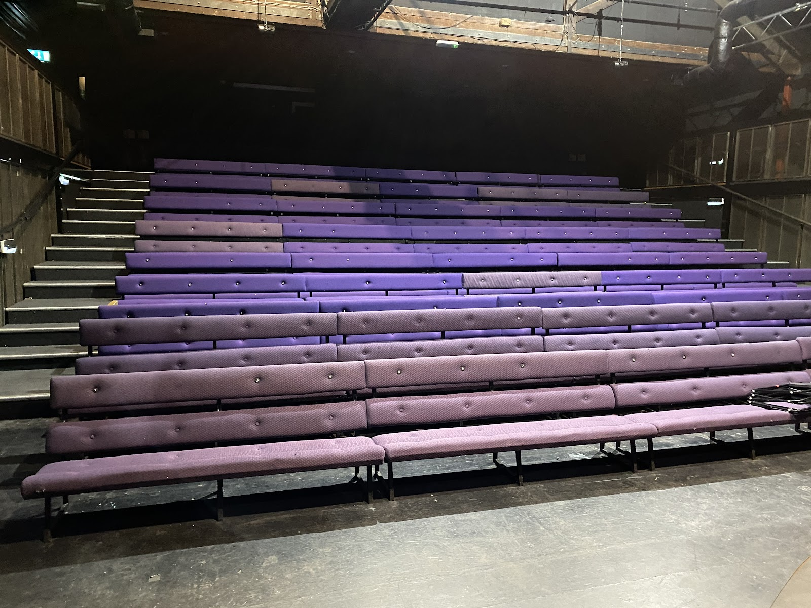 The seats are cushioned benches. The entrance to the venue is from the top of the steps of the seating rake. The accessible entrance is to the right hand side.