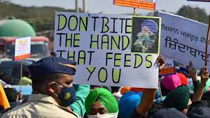 "Farmer holding sign which reads ""Don't Bite the Hand That Feeds You"""