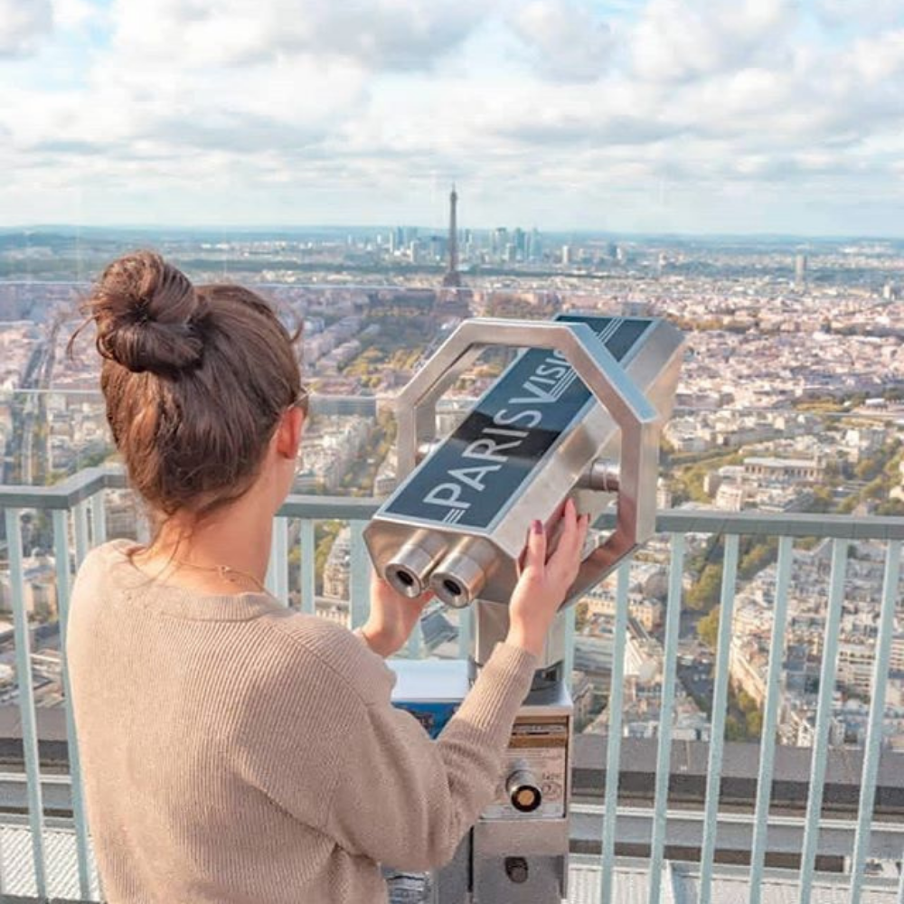 A woman looking at the view through a telescope from the second floor of the Eiffel Tower