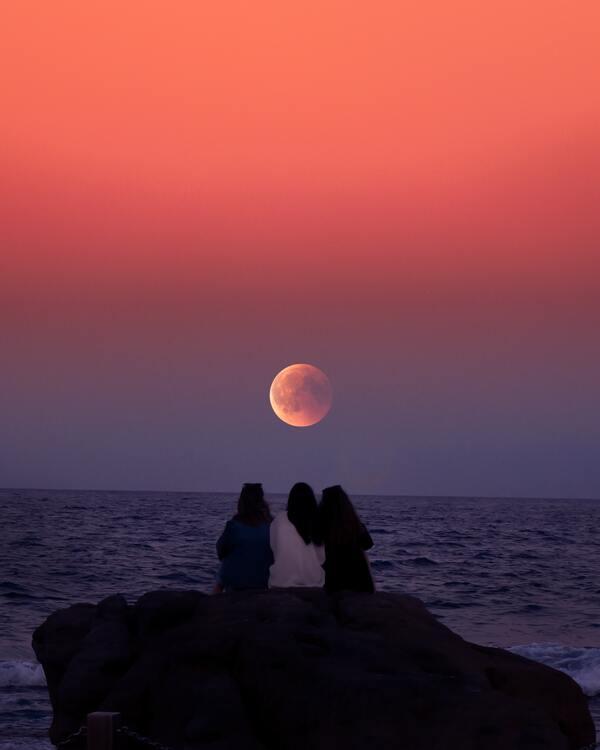 foto de três amigas vendo a lua durante o por-do-sol