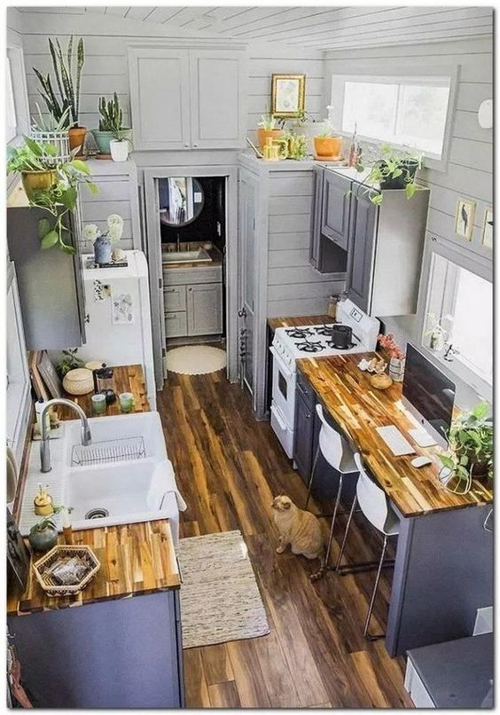 grey tiny home interior with grey kitchen cabinets, wood floors, wood countertops, shiplap walls and small desk area in the kitchen layout - tiny home kitchen - tiny house layout - tiny house kitchen ideas