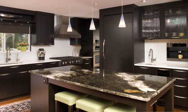 modern dark brown kitchen cabinets with granite island countertop and mini pendant lighting. glass doors and chrome hardware make the cabinets shine in this contemporary design