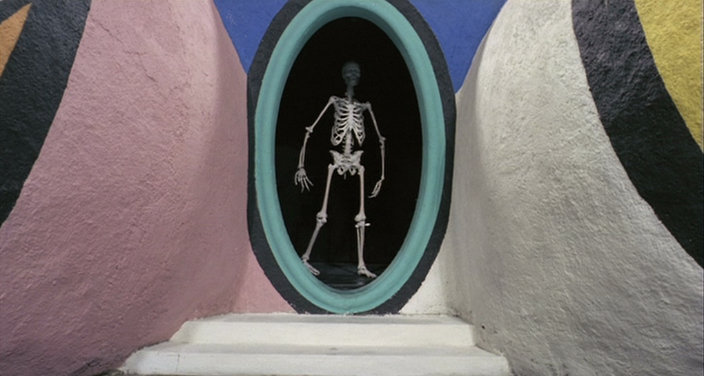 """the picture is a still from the film depicting the film's reproduction of the 1966 sculpture """"Hon - en katedral"""". It's a closeup of the sculpture's door-sized entry which is located where the vagina would be. Instead of a normal opening as the original sculpture had, the reproduction is now open without its teeth, while showcasing a full length human skeleton standing in the opening. Underneath the opening, two white-coloured steps are seen and on each side of the opening are the sculpture's thighs starting. They're painted in a variety of colours, including white, black, yellow, pink, orange and blue. Each section of colour is painted within a block and clearly separate from each other"""