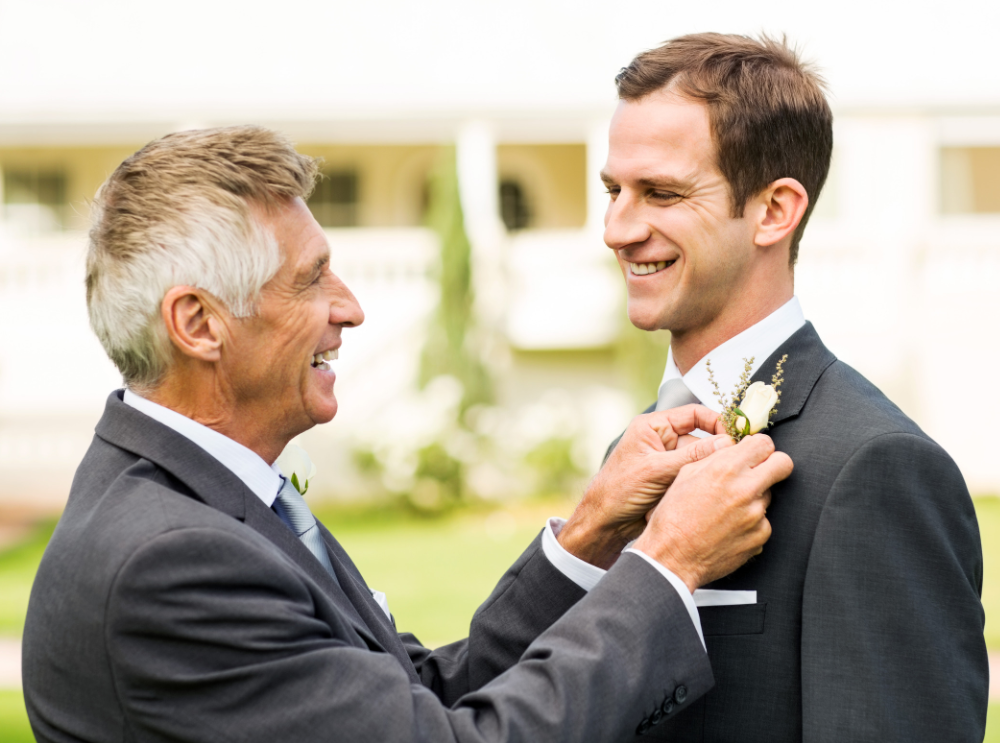 The father of the groom is placing a white corsage on the groom's chest.