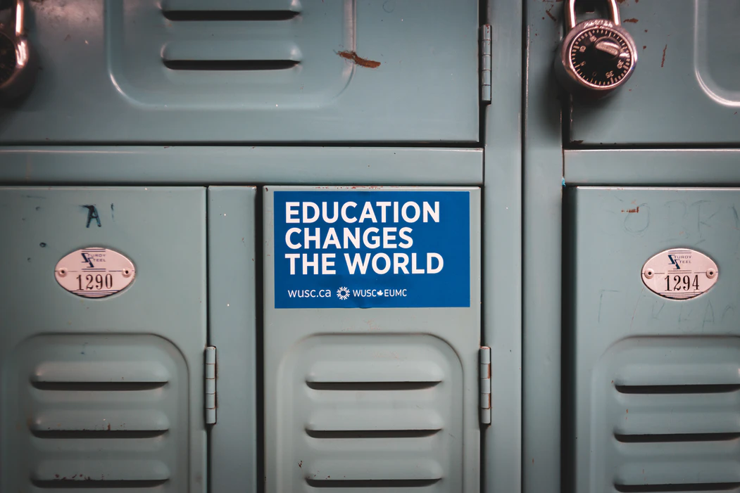 Grey locker, with visible copper lock and a sticker that says 'education changes the world' stuck on it.