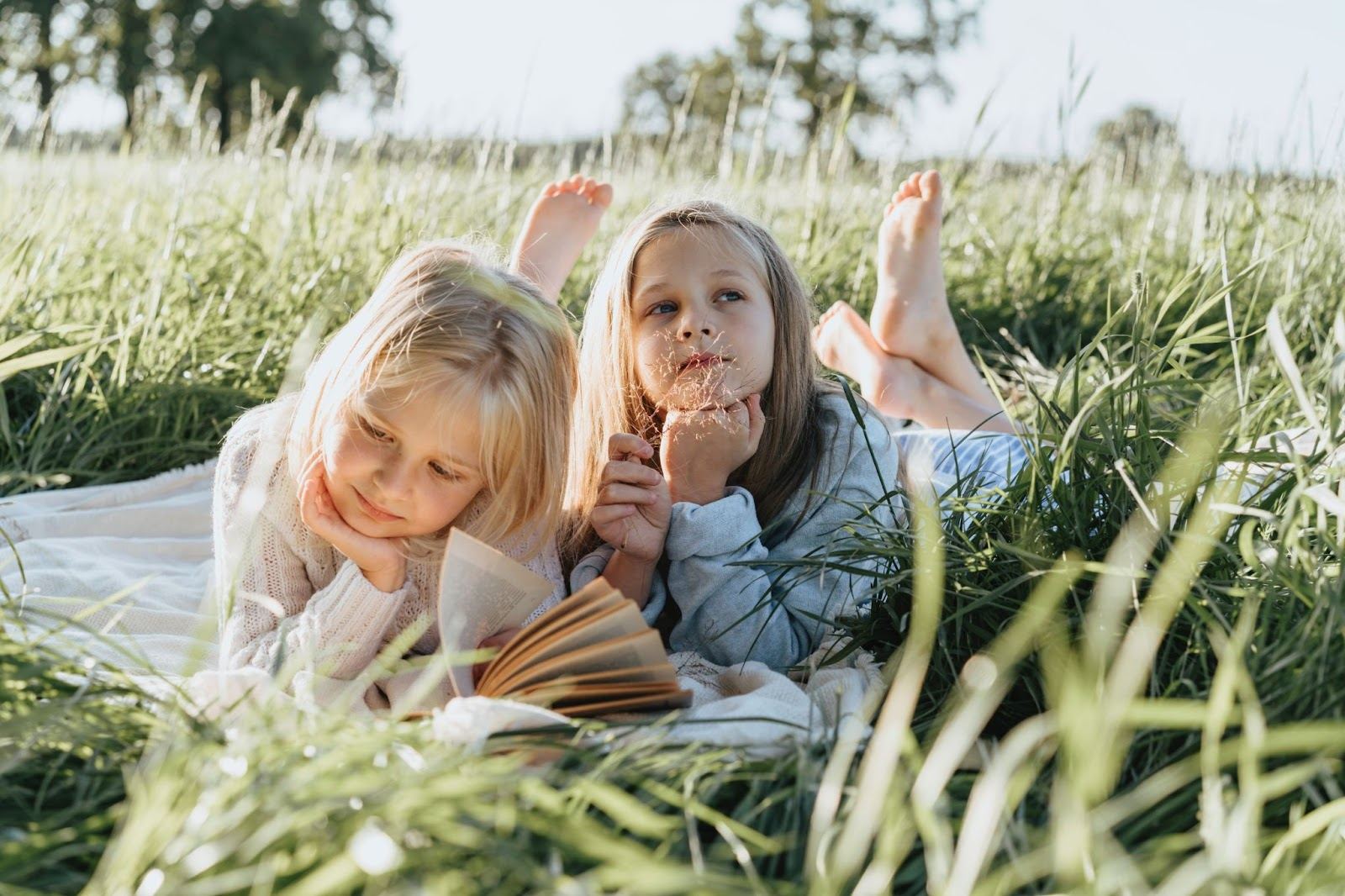 Two young girls of around five years old lay on the grass. One girl is reading a book, while another looks at the sky.