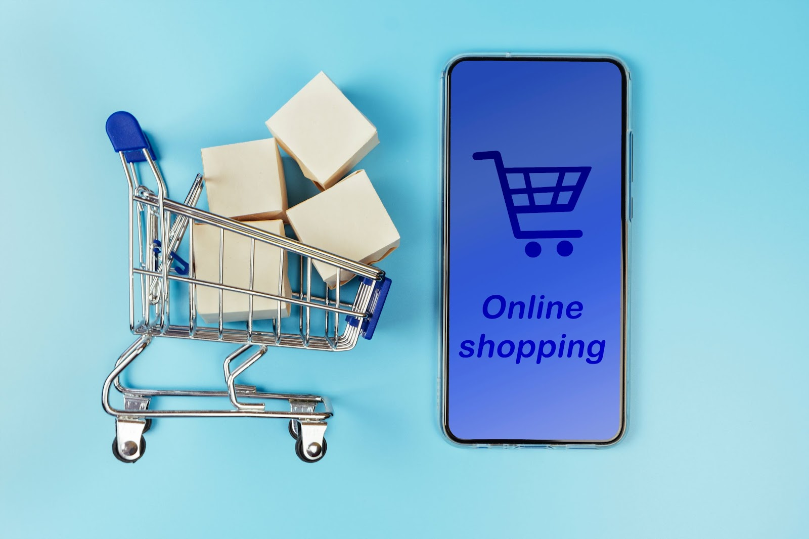 tiny shopping cart next to mobile phone showing e-commerce