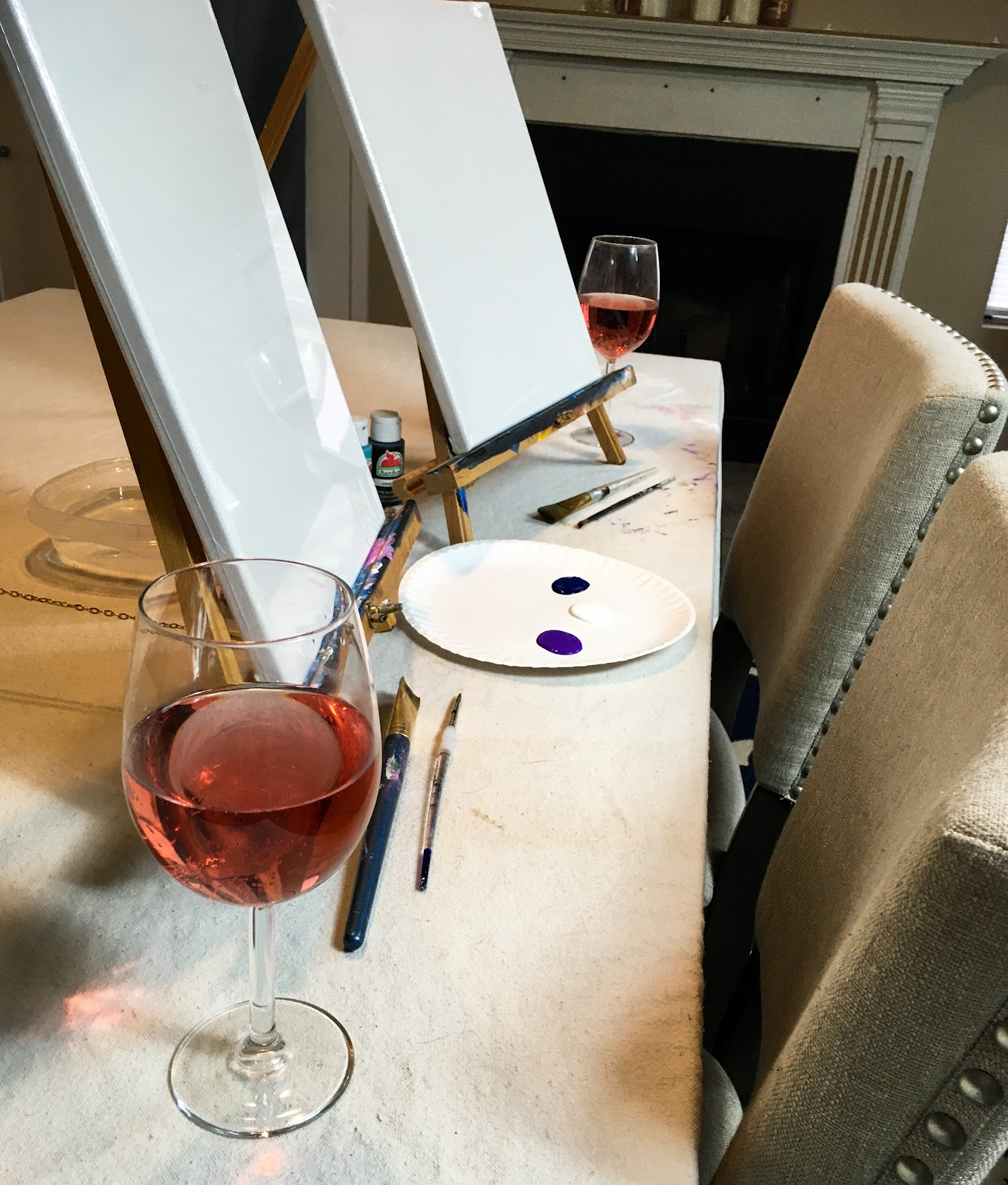 two easels and wine glasses with canvas
