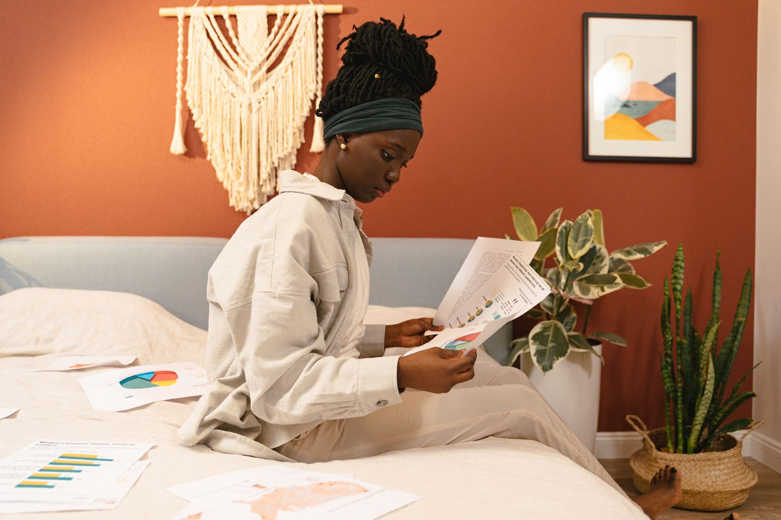 A teenage girl sits on a bed, reading graphs.