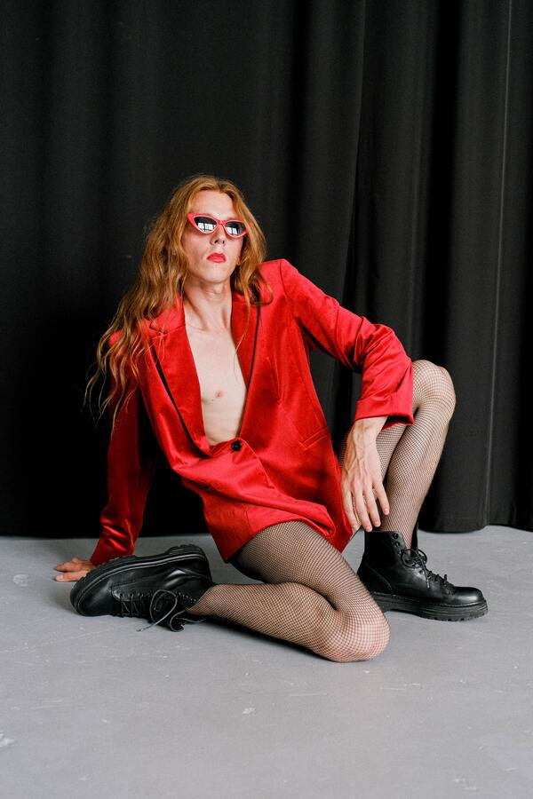 Homem queer e ruivo usando meia arrastão e um terninho curto vermelho, sentado no chão