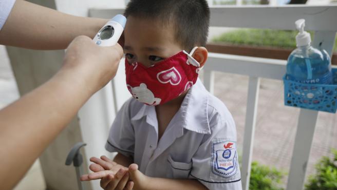 Enfermera tomándole la temperatura a su hijo