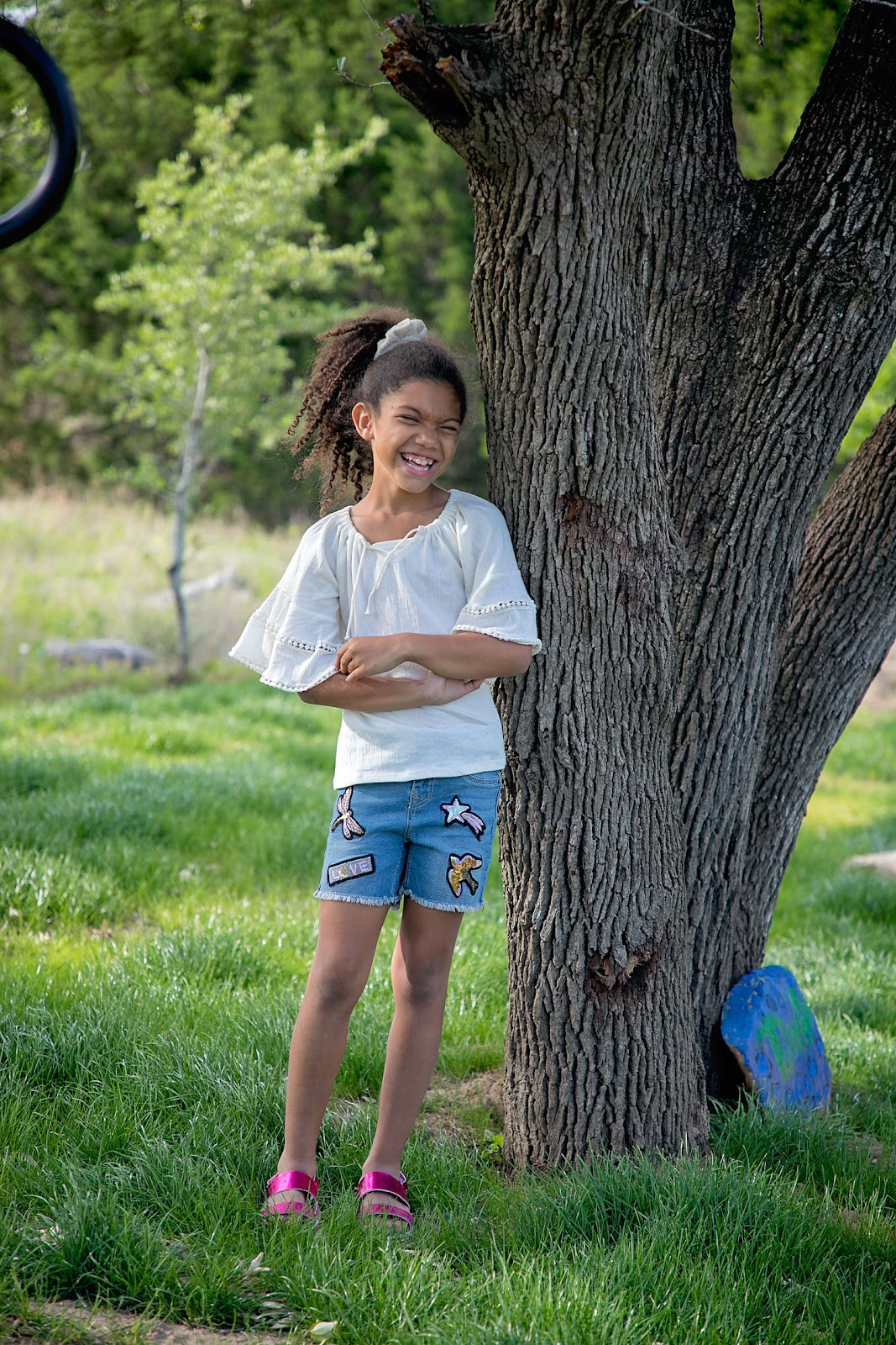 Little biracial girl standing in front of a tree and laughing. Stitch Fix kids outfit. Jean shorts and blouse.