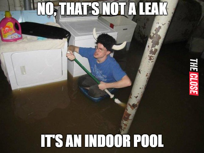 Man clearing flooding in the storage space of his house