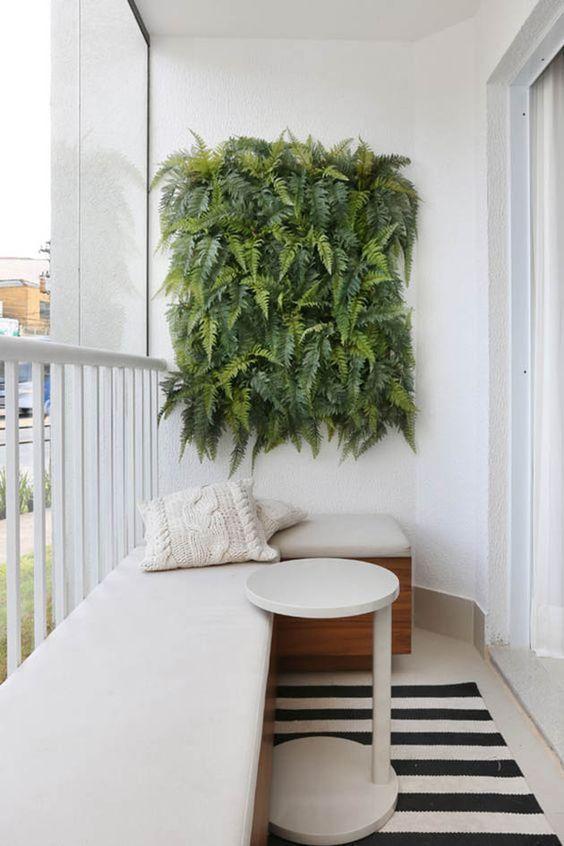 Varanda com projeto minimalista e clean destacou com painel de plantas, móvel planejado de sofá de madeira com estofado branco, mesinha de centro e tapete listrado.