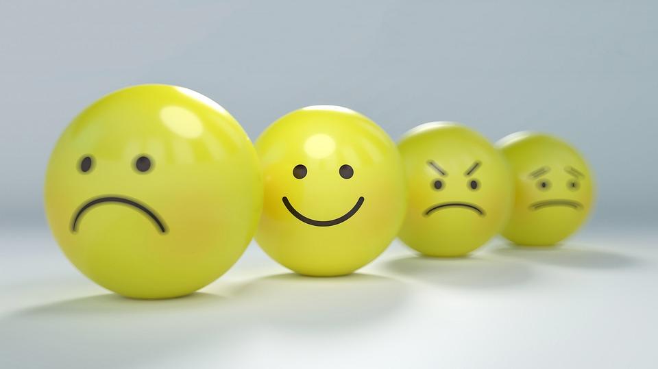 Quatro bolas amarelas, cada uma contendo uma expressão diferente. Da frente para trás: triste, feliz, zangado e chateado.